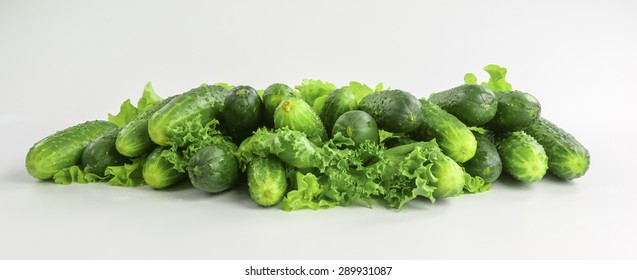 heap of fresh cucumbers and lettuce on white background