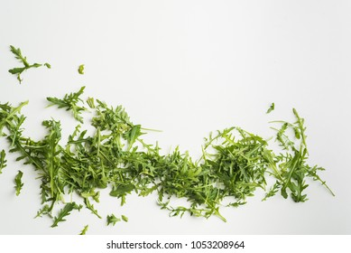 Heap of fresh green arugula on white table. Arugula is rich in vitamins and trace elements. Top view.