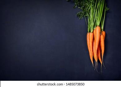 A heap of fresh organic carrot on black background.