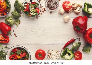 Heap of fresh organic tasty vegetables and salads background. Healthy natural food on white wooden table, cooking ingredients, organic vegetarian harvest, top view