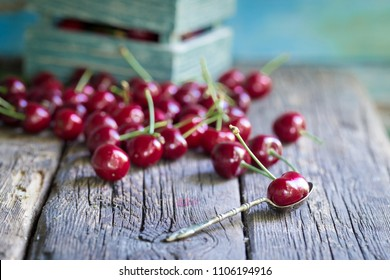 Heap of fresh picked cherries on a old wooden table. Vintage silver spoon on foreground.