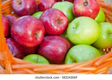 Heap of fresh red and green apples in a basket