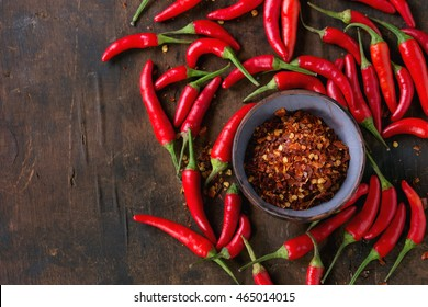Heap of fresh red hot chili peppers with ceramic bowl of dry chilli flakes over old wooden textured background. Spicy theme. Top view