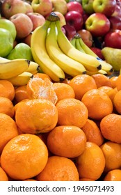 A heap of fresh ripe mandarin fruits, bananas and apples are on display on trays in the market and draw attention to the sale. Vertical image, selective focus.