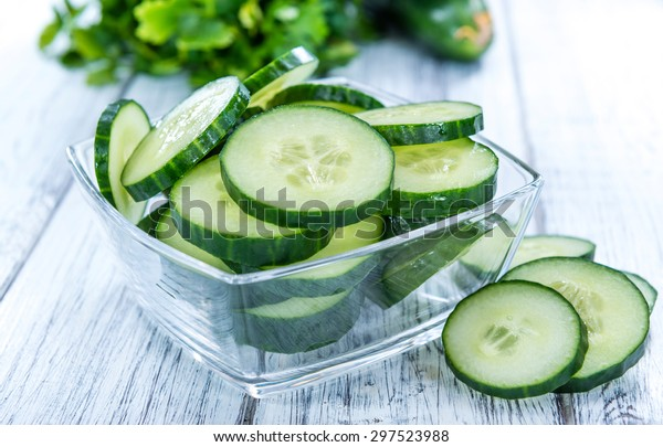 Heap of fresh sliced Cucumbers on an old wooden table