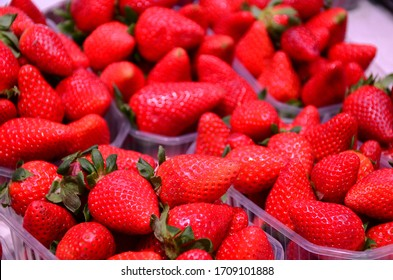 Heap of fresh strawberries in baskets ready for sale at marketplace.