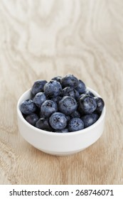 heap of fresh washed blueberries in white bowl on wood table