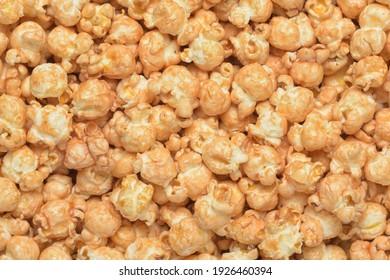 Heap of fresh yellow cooked caramel crunch popcorn background macro shot.