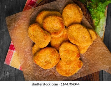Heap Fried Nuggets from chicken poultry meat on paper, ketchup for Nuggets, lettuce leaves. Vintage gray wooden wooden background. Top view