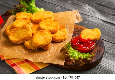 Heap Fried Nuggets from chicken poultry meat on paper, ketchup for Nuggets, lettuce leaves. One Nuggets   in ketchup. Vintage gray wooden wooden background.