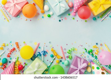 Heap of gift or present boxes, balloons, holiday supplies and confetti on blue table top view. Birthday party background.