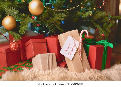 Heap of gift-boxes by Christmas tree