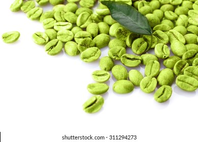 Heap of green coffee beans with leaf isolated on white