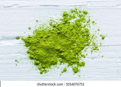 Heap of green matcha tea on white wooden background, free form, view from above, closeup
