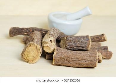 Heap of ground liquorice sticks isolated on wood (Also called as Glycyrrhiza acanthocarpa, or glabra liquorice)