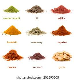 Heap ground Svanuri marili, dill seed, adjika, turmeric, rosemary, paprika, saffron, sumach and garlic isolated on white background