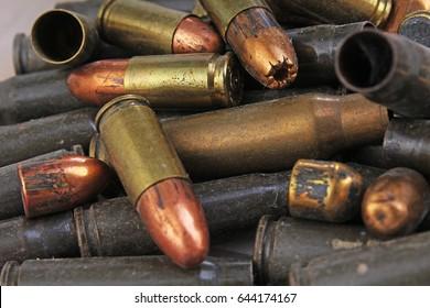 Heap of gun bullets. Weapon Cartridge case sleeve background texture, 7.65, and 9mm. Weapon cartridge sleeves.Gun bullet pattern close up.