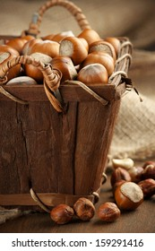 Heap of hazelnuts in basket with burlap on wood.