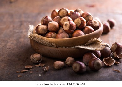 Heap Hazelnuts with broken shell on an old wooden table. Copy space for text