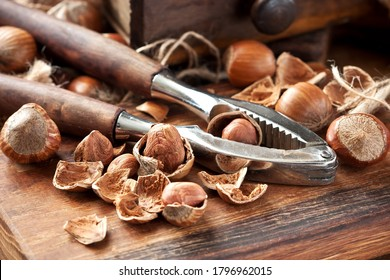 Heap hazelnuts on wooden board with nutcracker  on  rustic background, selective focus with  shallow depth of field