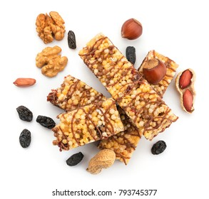 Heap of healthy muesli energy bars with nuts and raisins on white background