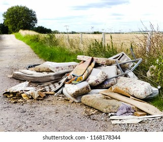 Heap of illegally dumped household rubbish left in a little used country lane. Environmental hazard, with furniture. mattresses and carpets. Fly tipped detritus. Oxfordshire.