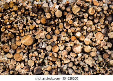 Heap of long wooden logs stacked horizontally close-up
