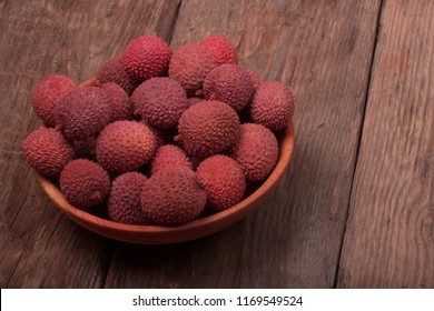 heap of Lychee in wooden plate on wooden background