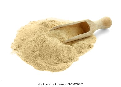 Heap of maca powder and wooden scoop, isolated on white