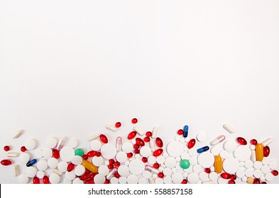 Heap of medicine tablets and pills different colors on white background. Copy space. Healthcare or medicament addiction concept. Empty space for text