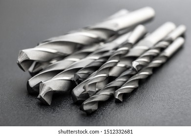 Heap of metal drill bits on black background.