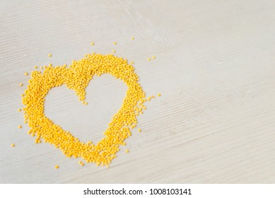 Heap of millet groats on the wooden background with copy space for your text. Top view. Raw Organic Healthy Millet. Pile of millet forming a heart, Love, Healthy eating concept
