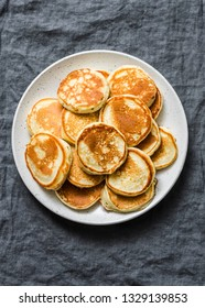 Heap of mini pancakes on a gray background, top view. Delicious breakfast, brunch, dessert