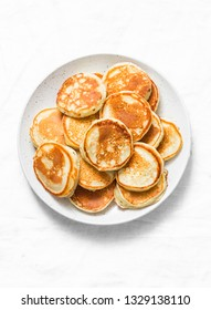 Heap of mini pancakes on a light background, top view. Delicious breakfast, brunch, dessert. Baby food