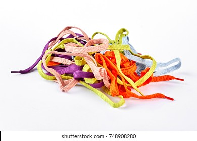 Heap of multicolored shoe laces. Pile of colorful strings for sport shoes isolated on white background.