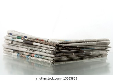 Heap of newspapers on shiny reflecting surface