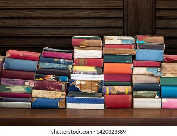 Heap up of old and damaged book on wooden table with wooden wall background