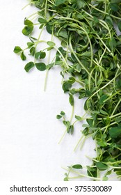 heap of organic and freshly harvested snow pea shoots or sprouts, over white kitchen cloth with copy space, top view, vertical