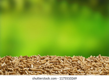 Heap of organic wood pellets over a blurred fresh green outdoor background with copy space for renewable energy and biofuel