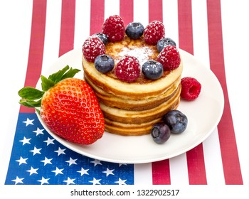 Heap of pancakes with berries on USA flag, isolated