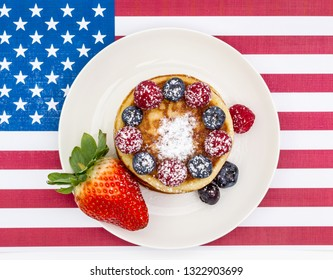 Heap of pancakes with berries on USA flag, top view