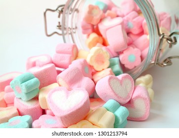 Heap of Pastel Color Heart Shaped and Flower Shaped Marshmallow Candies Scattered from a Glass Jar onto White Table