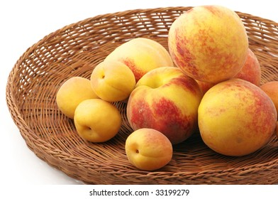 Heap of peaches and apricots in wicker tray on white background.