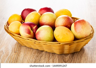 Heap of plums, apricots and nectarines in wicker basket on wooden table