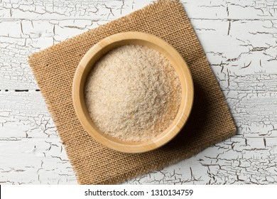 Heap of psyllium husk also called isabgol in wooden bowl on white table background. Psyllium husk is fiber derived from the seeds of Plantago ovata plant found in India. Flat lay from above.