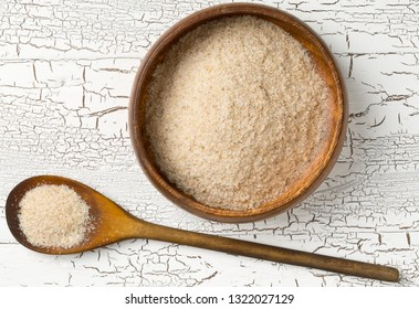 Heap of psyllium husk also called isabgol in wooden bowl and spoon on white table background. Psyllium husk  is fiber derived from the seeds of Plantago ovata plant found in India. Flat lay from above