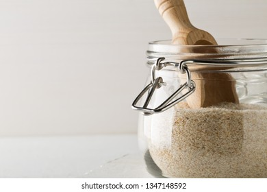 Heap of psyllium husk also called isabgol in glass jar with wooden scoop on white table background. Psyllium huskis fiber derived from the seeds of Plantago ovata plant found in India. Selective focus
