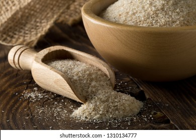 Heap of psyllium husk in wooden scoop and bowl on table. Psyllium husk also called isabgol is fiber derived from the seeds of Plantago ovata plant found in India. Selective focus.