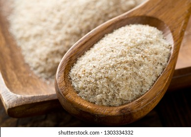 Heap of psyllium husk in wooden spoon and bowl on table. Psyllium husk also called isabgol is fiber derived from the seeds of Plantago ovata plant found in India. Selective focus.