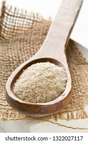 Heap of psyllium husk in wooden spoon on burlap. Psyllium husk also called isabgol is fiber derived from the seeds of Plantago ovata plant found in India. Selective focus.